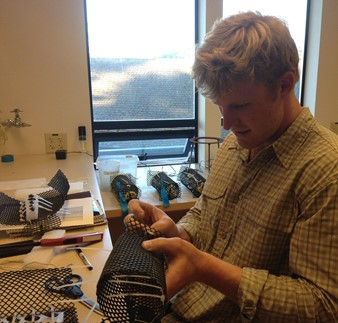 Sam LaFramboise places mussels in mesh enclosures. (Photo credit Laura Newcomb)