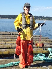 Molly Roberts, pictured at a mussel farm, estimated the cost of byssus from the experimental data using a Scope For Growth framework. (Photo credit: Hilary Hayford)